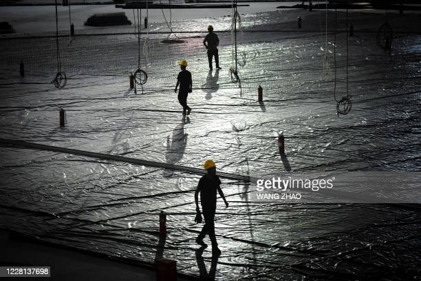 Workers walk inside the underconstruction National Speed Skating Oval the venue for speed skating events at the Beijing 2022 Winter Olympics in...