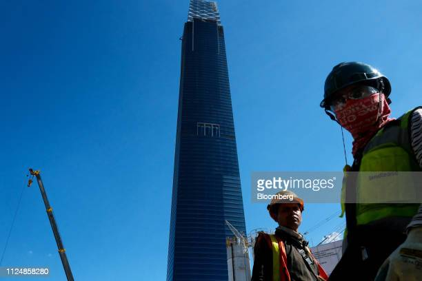 Workers walk near the under construction Exchange 106 building on the site of the Exchange TRX precinct in Kuala Lumpur Malaysia on Tuesday Feb 12...