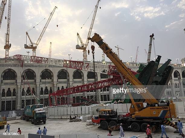 Workers walk next to the crane that collapsed the day before at the Grand Mosque on September 12 2015 in Saudi Arabia's holy Muslim city of Mecca...