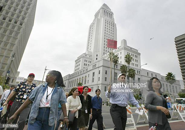 Workers walk north to a safe zone as they evacuate Los Angeles City Hall and other buildings in the downtown Civic Center area as part the city's...