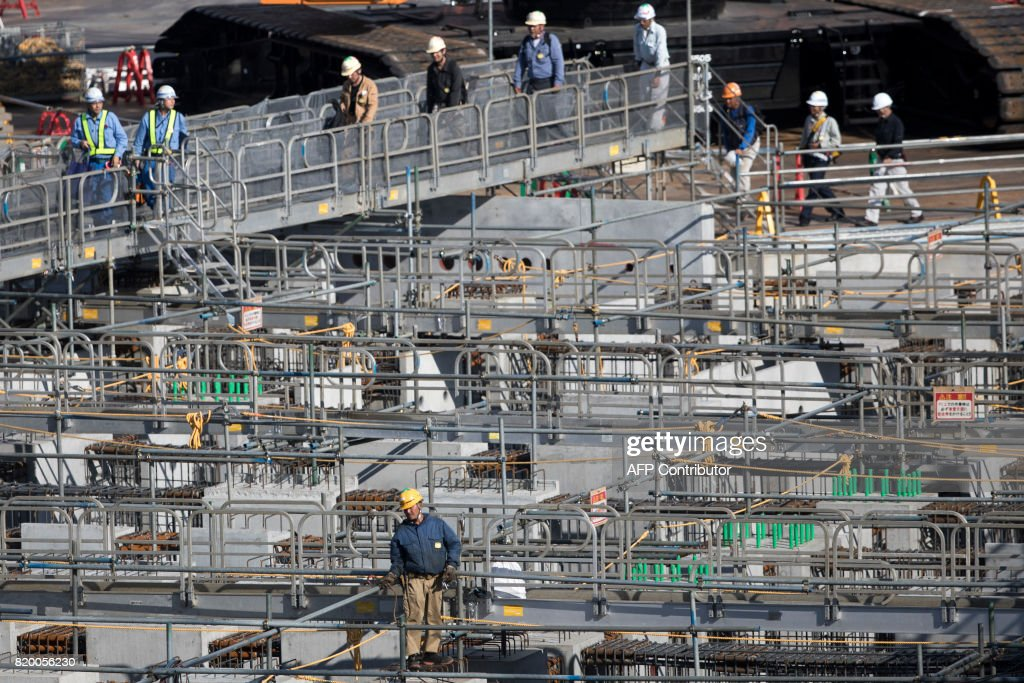 Workers walk on a bridge at the construction site for the National Stadium, venue for the upcoming Tokyo 2020 Olympic Games, in Tokyo on July 21, 2017. The suicide of a 23-year-old worker on Tokyo's Olympic stadium was due to overwork, his family said on July 21, as Japan races to finish building venues for the 2020 Games. / AFP PHOTO / Behrouz MEHRI