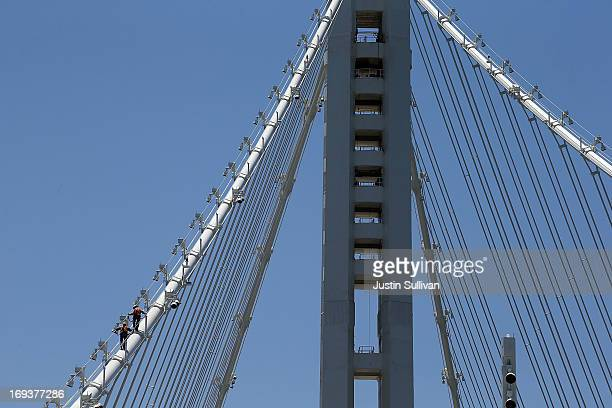 Workers walk on a cable of the newly constructed eastern span of the San FranciscoOakland Bay Bridge on May 23 2013 in Oakland California Bridge...