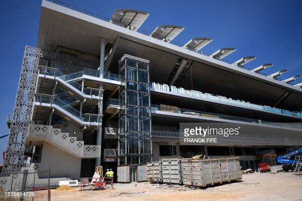 Workers walk on the construction site of the Philippe Chatrier central tennis court and of its newly built roof at the Roland Garros stadium in Paris...