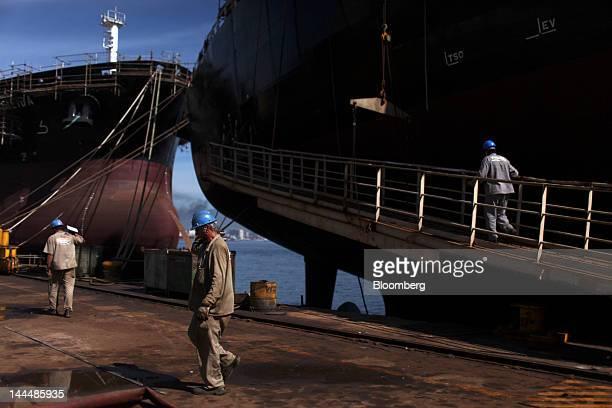 Workers walk on the dock near the Romulo Almeida vessel left and the Jose de Alencar vessel both Petroleo Brasileiro SA oil tankers under...