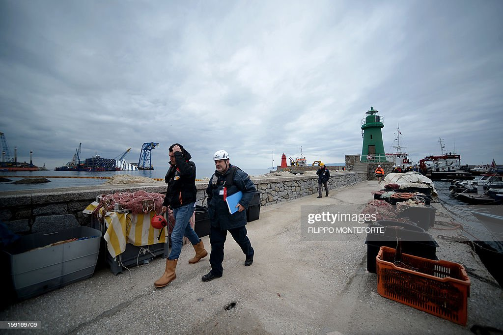 Workers walk on the port as the Costa Concordia cruise ship lays aground near the port on January 9, 2013 on the Italian island of Giglio. A year on from the Costa Concordia tragedy in which 32 people lost their lives, the giant cruise ship still lies keeled over on an Italian island and its captain Francesco Schettino has become a global figure of mockery.