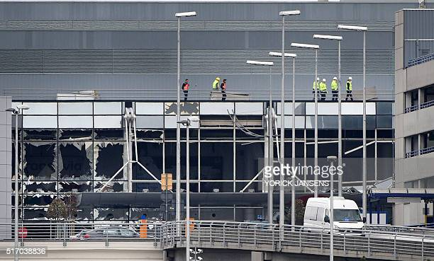 Workers walk on the roof of the damaged facade of Brussels airport in Zaventem on March 23 one day after two massive suicide blasts by men with bombs...
