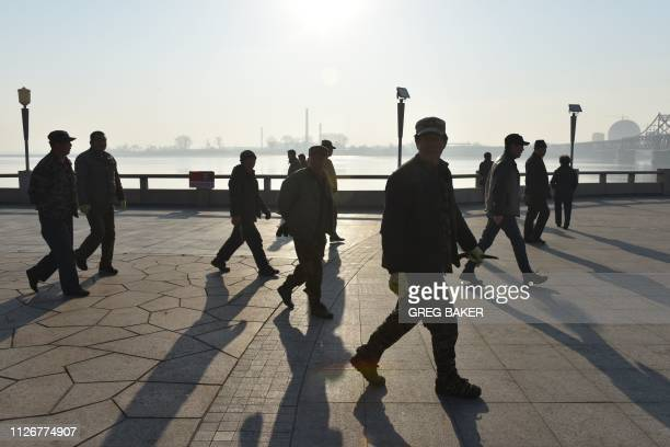 Workers walk on the waterfront in the border city of Dandong, in China's northeast Liaoning province, with the North Korean city of Sinuiju behind on...