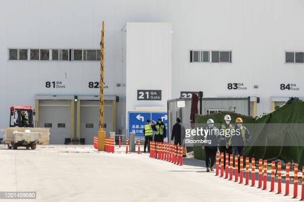 Workers walk out from the Tesla Inc Gigafactory in Shanghai China on Monday Feb 17 2020 Tesla has fully resumed deliveries of its Chinabuilt model 3...