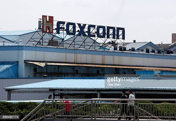 Workers walk outside Hon Hai Group's Foxconn plant in Shenzhen China on Wednesday May 26 2010 Hon Hai is the parts supplier for many hitech companies...