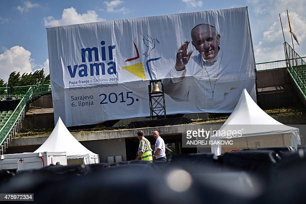 Workers walk past a banner with a picture of Pope Francis at Sarajevo city stadium on June 5 a day ahead of the his visit Pope Francis flies into...