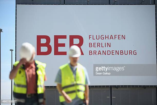 Workers walk past a billboard at the unfinished new BER Willy Brandt Berlin Brandenburg International Airport on June 2 2014 in Schoenefeld Germany...