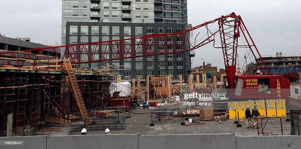 Workers walk past a construction crane after it collapsed on January 9, 2013 in the Queens borough of New York City. The crane collapse injured seven construction workers on the site in the Long Island City neighborhood.