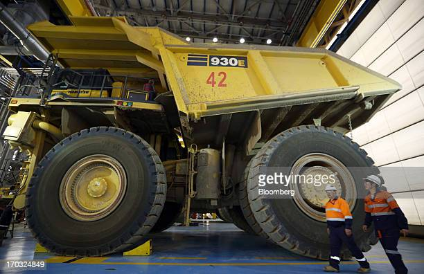 Workers walk past a Komatsu Ltd dump truck inside the truck shop at the Oyu Tolgoi coppergold mine jointly owned by Rio Tinto Group's unit Turquoise...