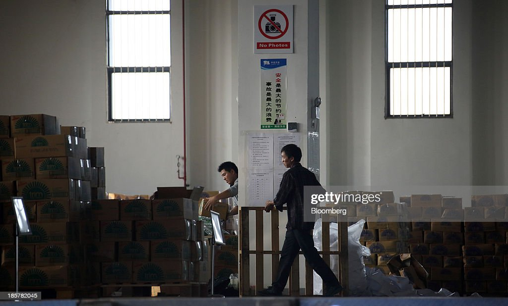 Workers walk past a storage area in a logistics center at China (Shanghai) Pilot Free Trade Zone's Pudong free trade zone in Shanghai, China, on Thursday, Oct. 24, 2013. The area is a testing ground for free-market policies that Premier Li Keqiang has signaled he may later implement more broadly in the world's second-largest economy. Photographer: Tomohiro Ohsumi/Bloomberg via Getty Images