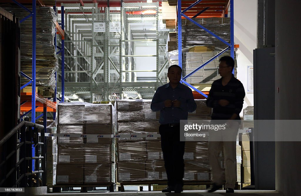 Workers walk past a warehouse in a logistics center at China