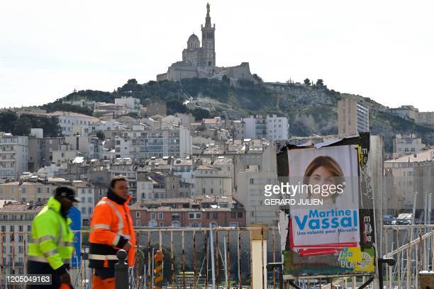 Workers walk past an electoral poster of Martine Vassal, member of the French right-wing party Les Republicains for the Marseille 2020 mayoral...
