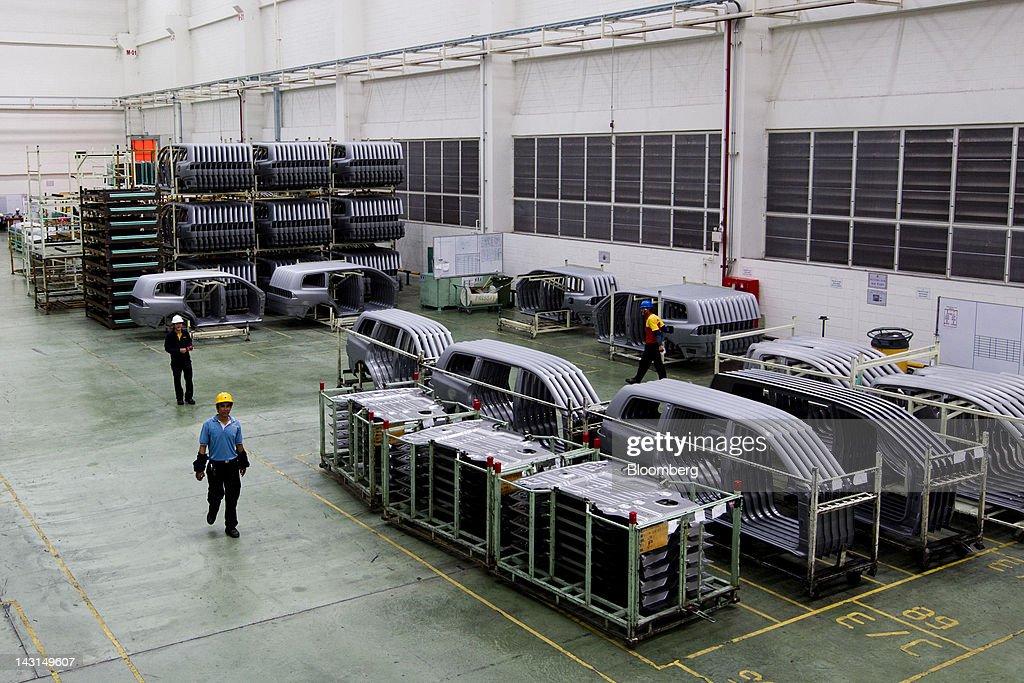 Workers Walk Past Car Parts Inside Mitsubishi Motors Corp S Factory