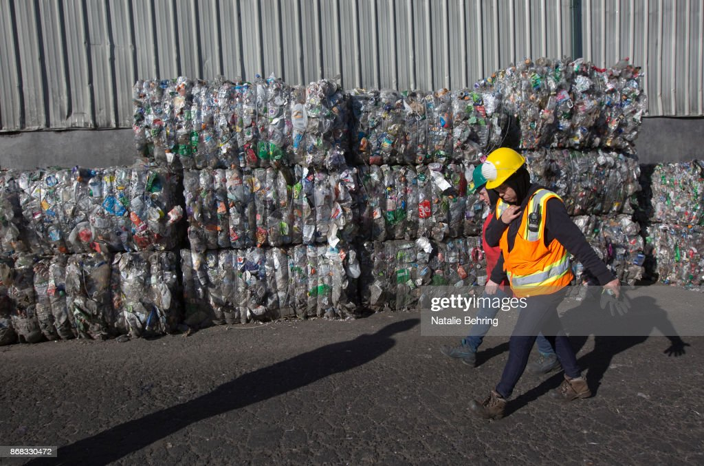 Workers walk past compressed blocks of plastic waste at Far West Recycling shows October 30, 2017 in Hillsboro, Oregon. For decades, shipping containers have been loaded with American scrap and waste and dispatched to China for recycling. But, the Chinese government is cracking down, and will no longer allow shipments of much of the mixed plastic and paper Americans throw in to recycling bins. The shipments are too often contaminated with other waste like dirty diapers.