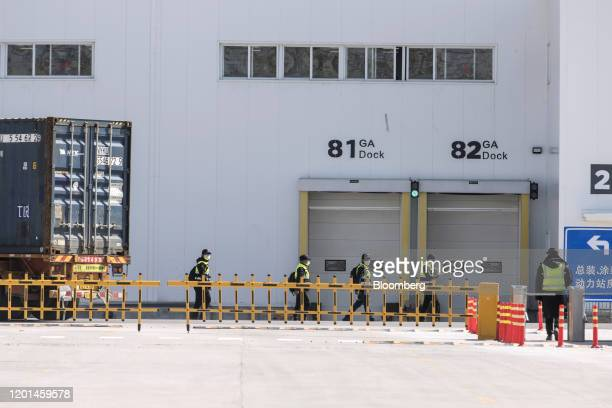 Workers walk past docks at the Tesla Inc Gigafactory in Shanghai China on Monday Feb 17 2020 Tesla has fully resumed deliveries of its Chinabuilt...