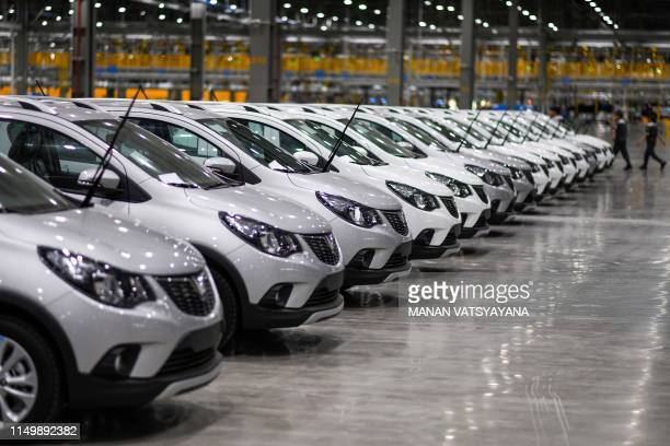 Workers walk past finished cars at the assembly plant of VinFast Vietnam's first homegrown car manufacturer in Haiphong on June 14 2019
