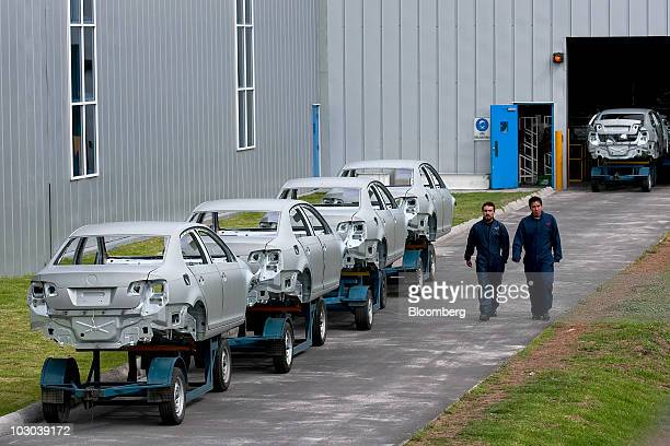 Workers walk past frames for Volkswagen AG's new Jetta compact sedan at the company's factory in Puebla Mexico on Thursday July 22 2010 The new Jetta...