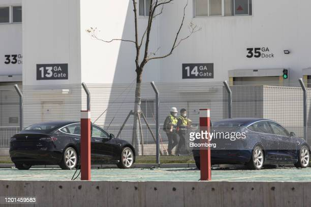 Workers walk past gates and vehicles at the Tesla Inc Gigafactory in Shanghai China on Monday Feb 17 2020 Tesla has fully resumed deliveries of its...