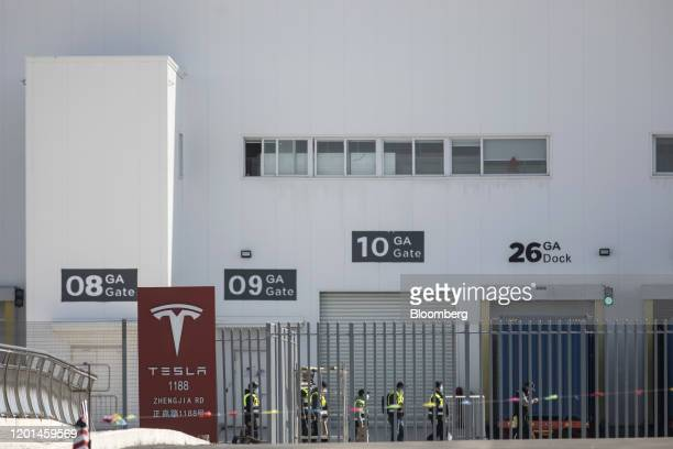 Workers walk past gates at the Tesla Inc Gigafactory in Shanghai China on Monday Feb 17 2020 Tesla has fully resumed deliveries of its Chinabuilt...