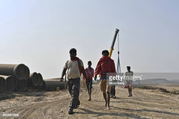 Workers walk past past pipes stacked at the project site for a 920squarekilometer industrial area located on the DelhiMumbai Industrial Corridor near...