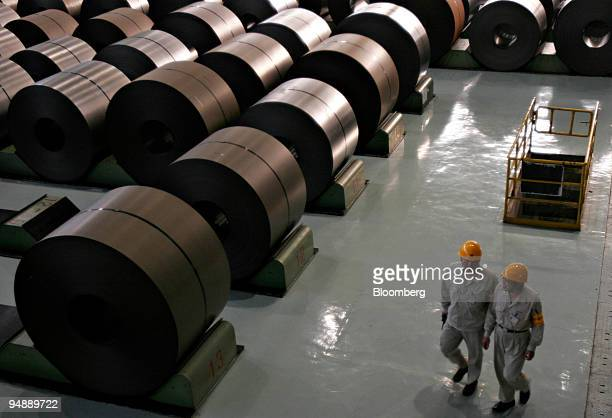 Workers walk past rolled steel at the BaosteelNSC/Arcelor Automotive Steel Sheets Co plant in Shanghai China Tuesday November 8 2005 The US asked the...