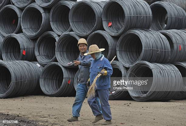 Workers walk past rolls of steel at a steel product market on May 15 2009 in Shenyang of Liaoning Province China According to the National Statistics...