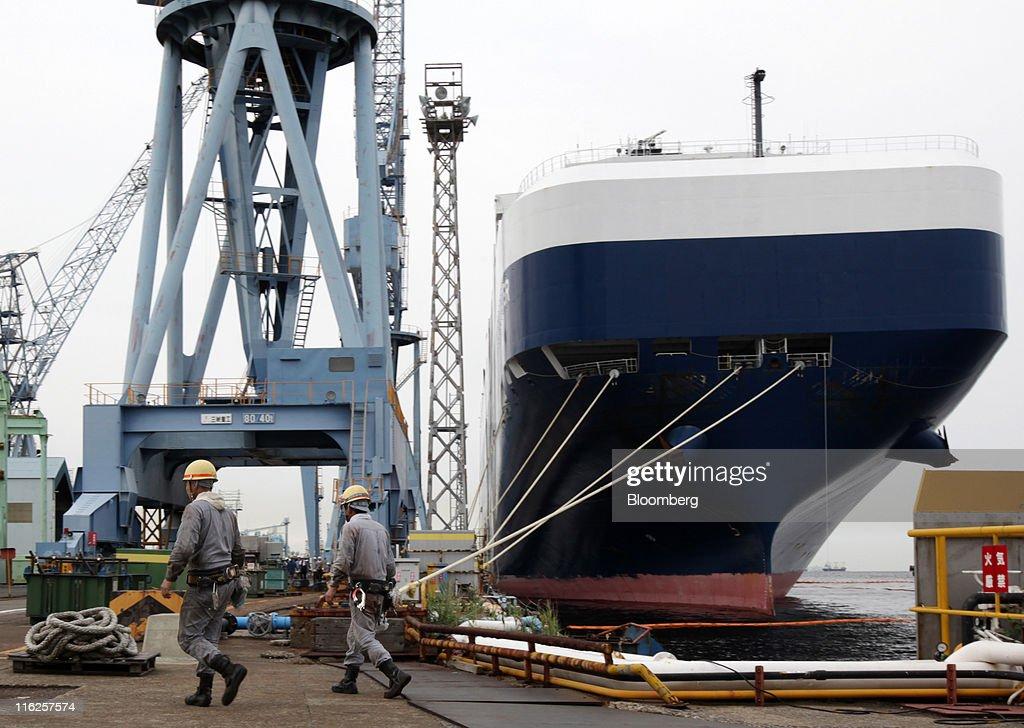 Workers walk past the Nippon Yusen K.K.'s car transporter ship, Auriga Leader, at Mitsubishi Heavy Industries Ltd.'s Honmoku plant in Yokohama city, Kanagawa prefecture, Japan, on Wednesday, June 15, 2011. Nippon Yusen K.K. is Japan's largest shipping line. Photographer: Tomohiro Ohsumi/Bloomberg via Getty Images