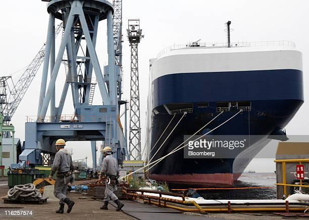 Workers walk past the Nippon Yusen KK's car transporter ship Auriga Leader at Mitsubishi Heavy Industries Ltd's Honmoku plant in Yokohama city...