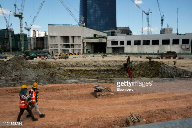 Workers walk past the under construction Exchange 106 on the site of the Exchange TRX precinct in Kuala Lumpur Malaysia on Tuesday Feb 12 2019 The...