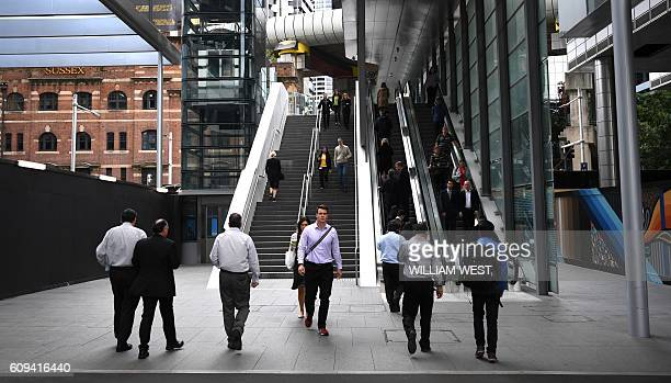Workers walk through the developing office and residental area of Barangaroo in Sydney's innercity on 21 September 2016 / AFP / WILLIAM WEST