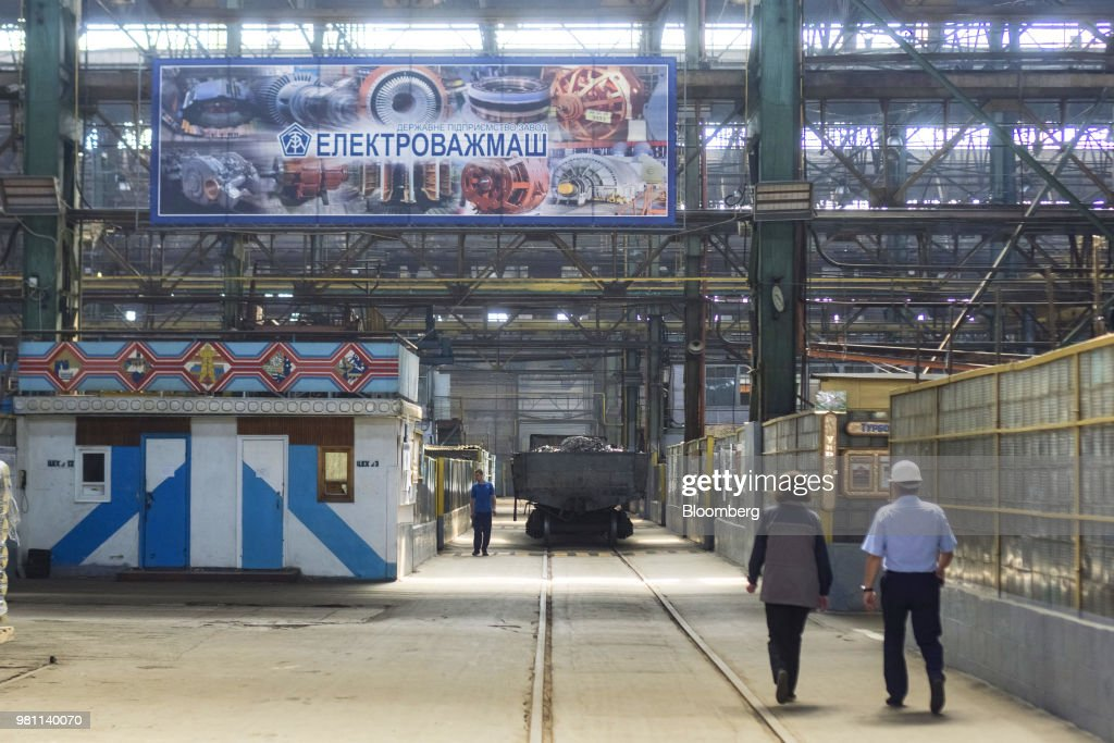 Workers walk through the generator manufacturing floor at the