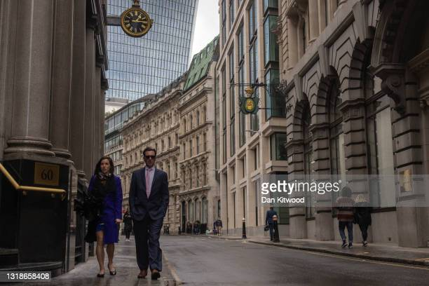 Workers walk through the square mile on May 18, 2021 in London, England. Workers have begun to return to the City of London as lockdown rules have...