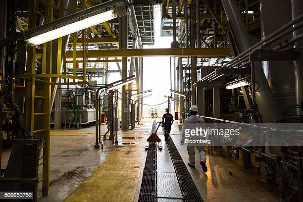 Workers walk through the Tullow Oil Plc Prof John Evans Atta Mills Floating Production Storage and Offloading vessel docked at the Sembcorp Marine...