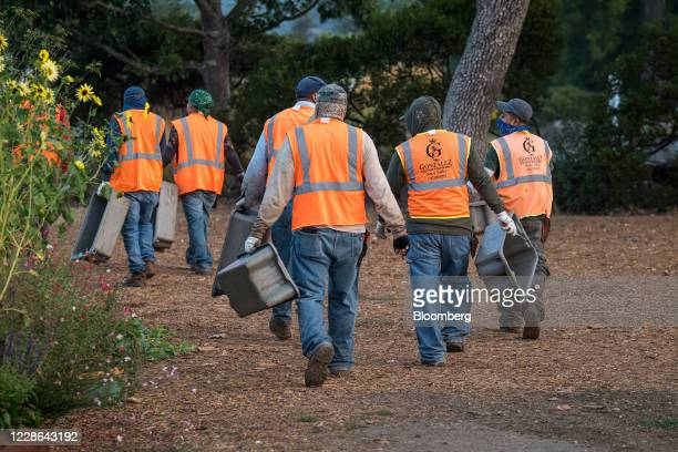 Workers walk towards a vineyard in Kenwood California US on Monday Sept 21 2020 Smoke from the LNU Lightning Complex wildfires may have damaged...