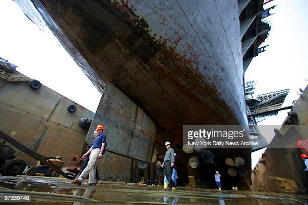 Workers walk under the keel of the World War 2 era aircraft carrier Intrepid as it sits in dry dock at Bayonne Dry Dock Repair Corp on the peninsula...