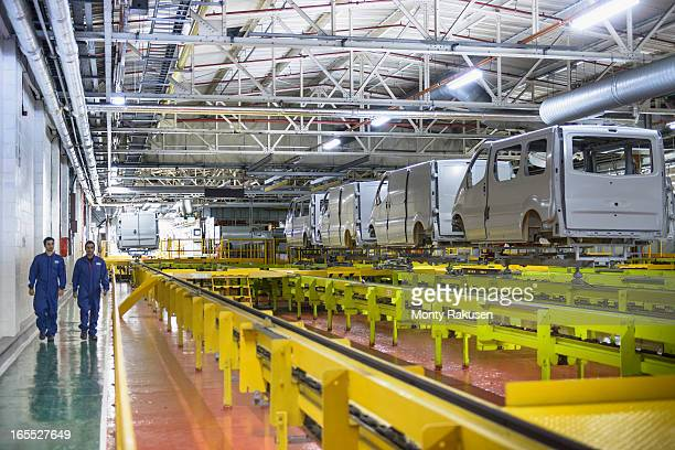 workers walking alongside vehicles in car factory - luton stock pictures, royalty-free photos & images