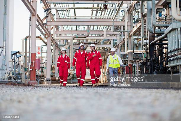 workers walking at chemical plant - gas refinery stock photos and pictures