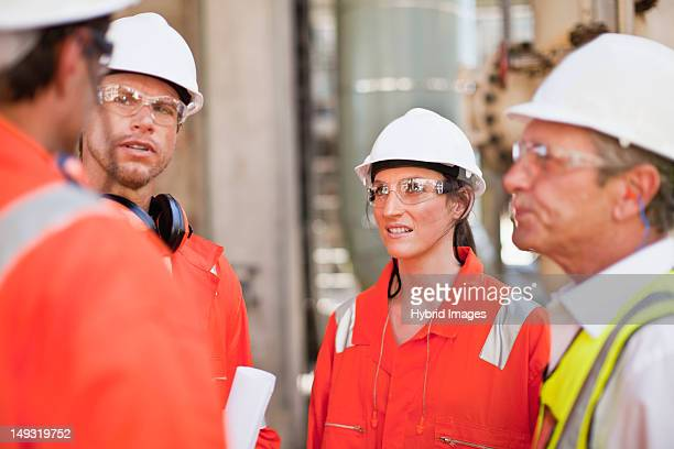 workers walking at oil refinery - power occupation stock photos and pictures