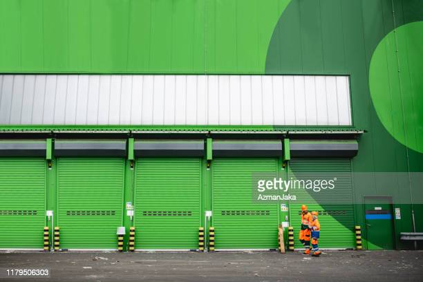 workers walking in recycling facility loading dock area - waste management stock pictures, royalty-free photos & images