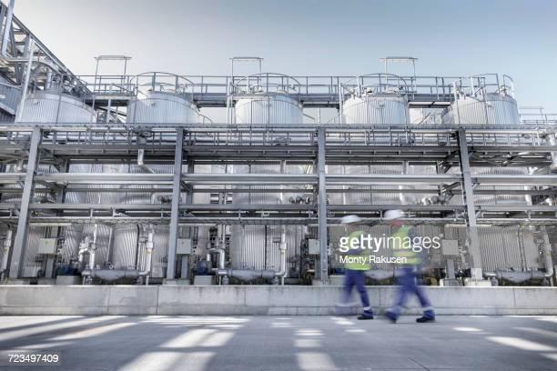 workers walking past process tanks in oil blending factory - ölindustrie stock-fotos und bilder