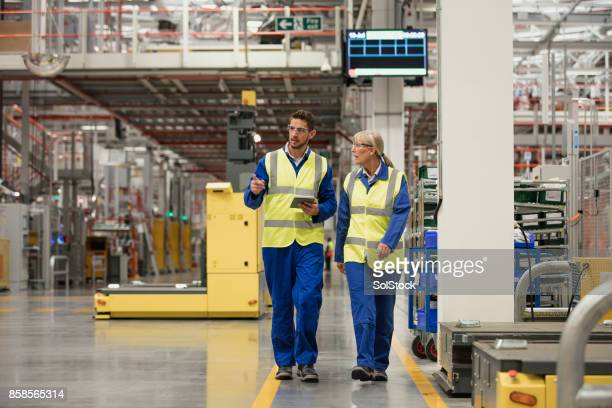 workers walking through a factory - social justice concept stock pictures, royalty-free photos & images