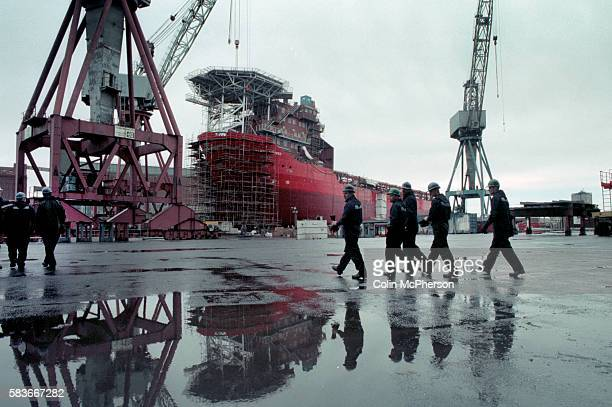 Workers walking towards a vessel at the Govan shipyard on the banks of the river Clyde in Glasgow. At the time of this photograph, the shipyard was...