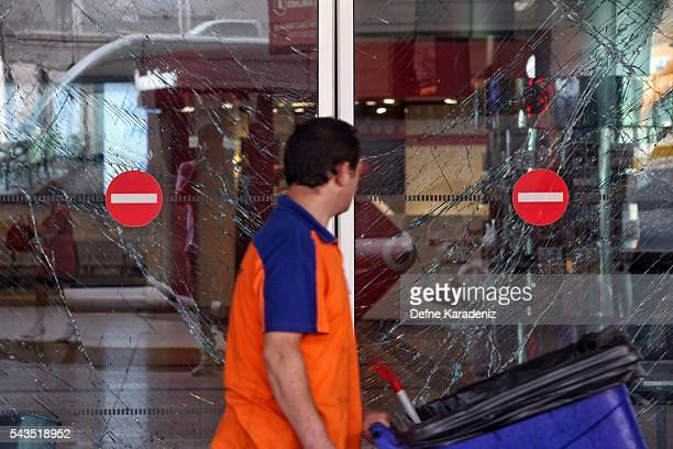 Workers walks past the broken windows from yesterday's blasts at Turkey's largest airport Istanbul Ataturk June 29 Turkey Three suicide bombers...