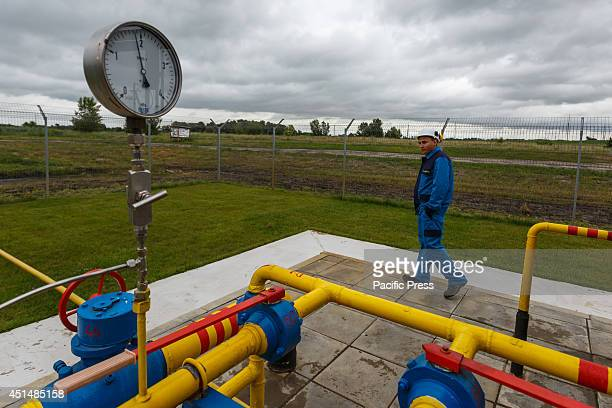 Workers walks past the gauge on the booster station gas condensate boosting compressor station ''EastPoltava'' near the village of Kovalivka Poltava...