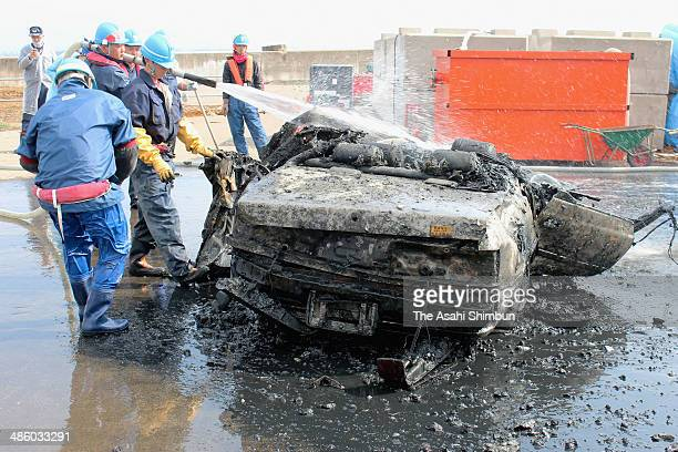 Workers wash a car in which possible human remains were found after begin loaded from the bottom of the sea at Yuriage Port on April 22 2014 in...