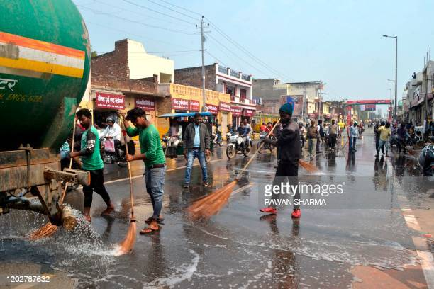 Workers wash a road with water near Kheria Airport in Agra on february 23 ahead of US President Donald Trump first official visit to India. - US...